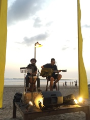 Musicians playing on the beach at sunset