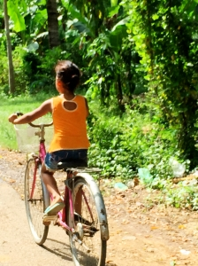 Cambodian girl riding thru the country side