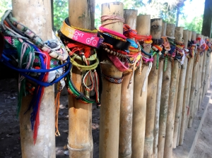 Prayer bracelets around a fenced in mass grave
